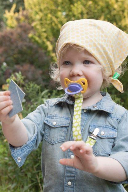 Kleinkind mit Schnuller am Schnullerband